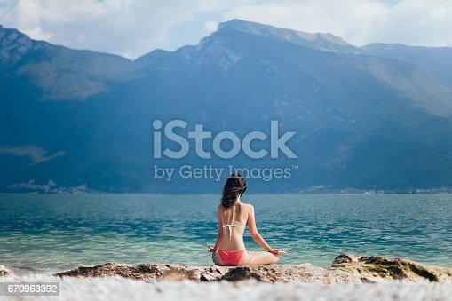 istock Woman meditating in Lotus Pose on beautiful beach of mountain lake Garda 670963392