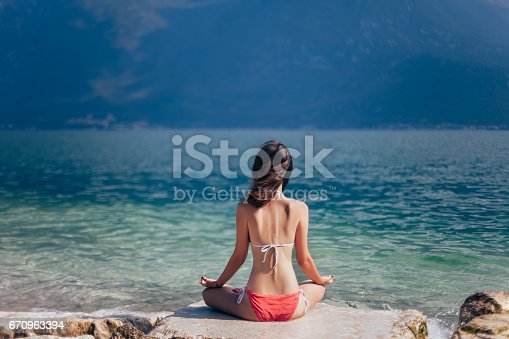 istock Woman meditating in Lotus Pose on beautiful beach of mountain lake Garda 670963394