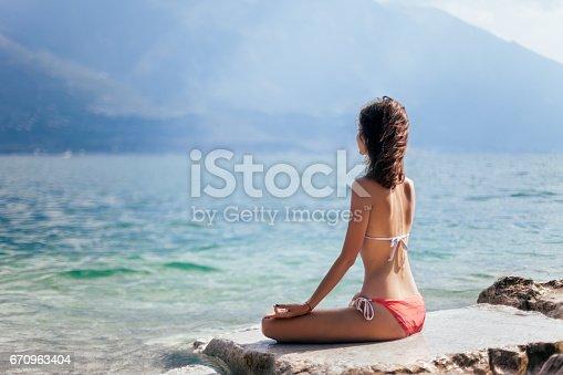 istock Woman meditating in Lotus Pose on beautiful beach of mountain lake Garda 670963404