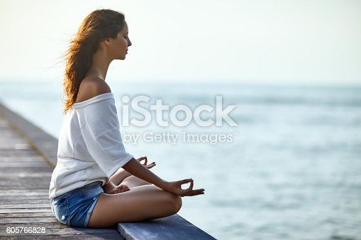istock Woman meditating in Lotus Pose on pier 605766828
