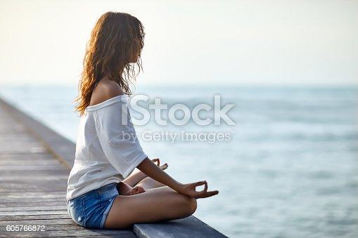 istock Woman meditating in Lotus Pose on pier 605766872