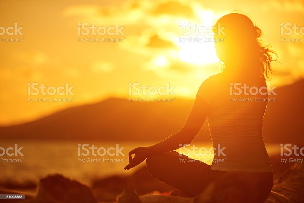 woman meditating in lotus pose on the beach at sunset stock photo
