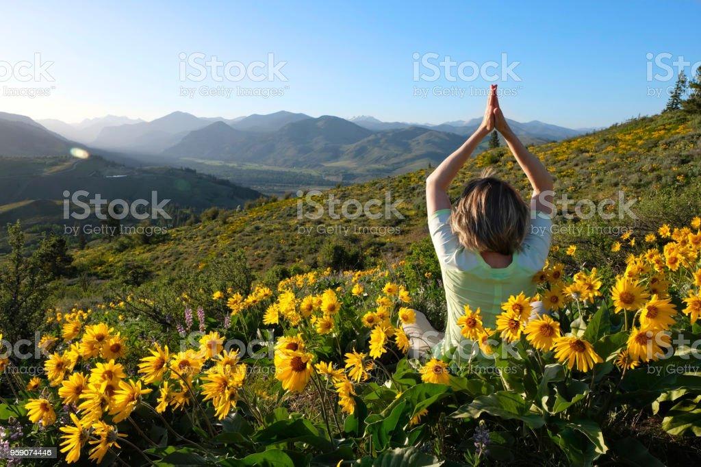 Frau in Weiden mit Sonnenblumen zu meditieren. – Foto