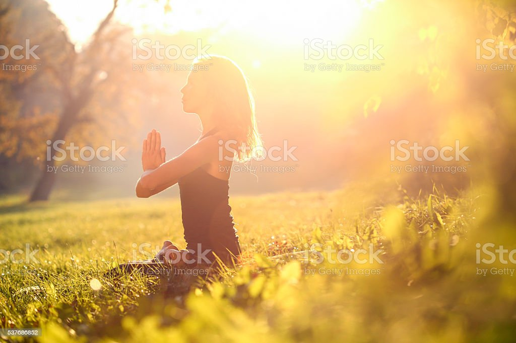 Woman meditating in nature stock photo