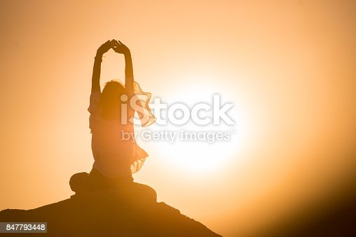 Woman in cross-legged position meditating over rocks in nature