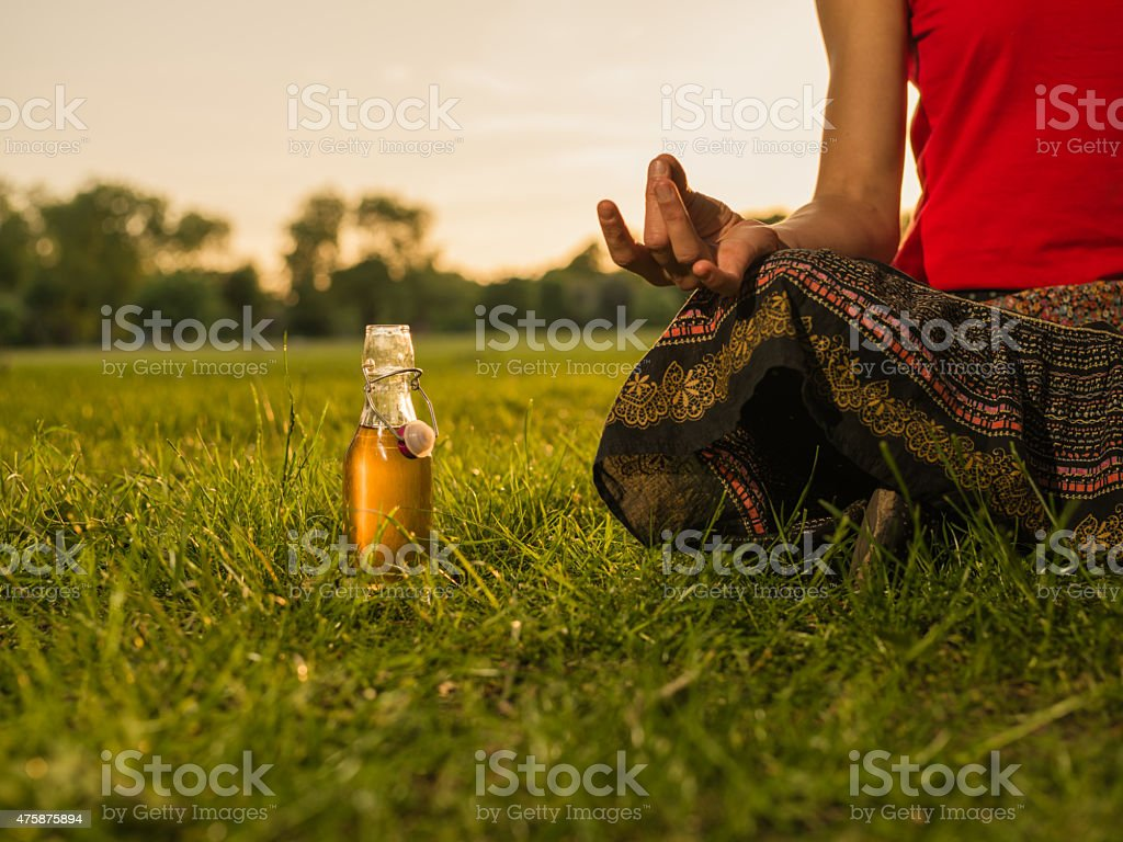 Woman meditating in park at sunset stock photo