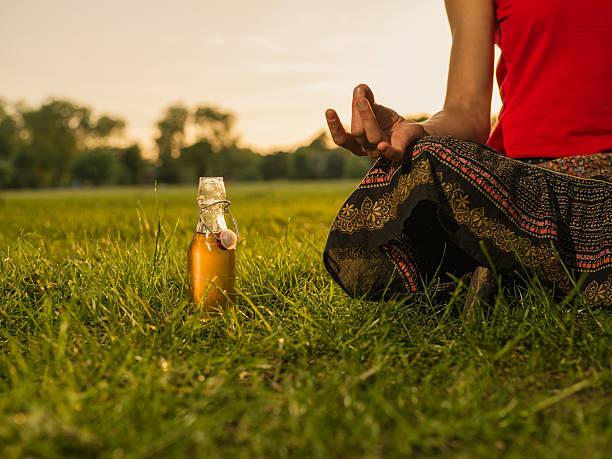 frau meditieren im park bei sonnenuntergang - bier gesund stock-fotos und bilder