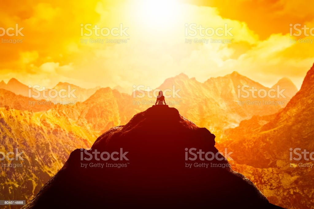 Woman meditating in sitting yoga position on the top of a mountains above clouds at sunset. stock photo