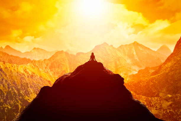 woman meditating in sitting yoga position on the top of a mountains above clouds at sunset. - mountain peak stock pictures, royalty-free photos & images