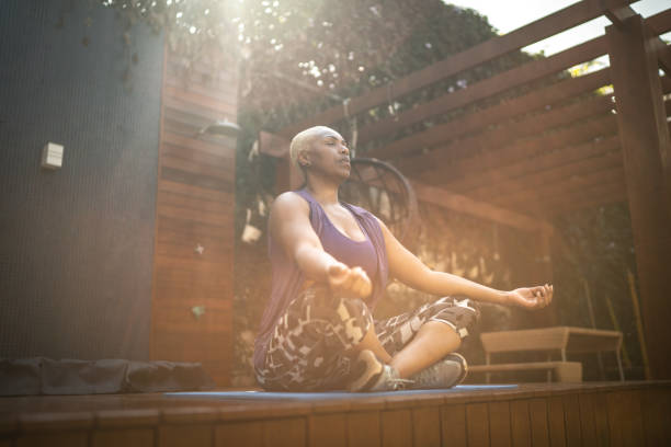 woman meditating in the backyard - meditation stock pictures, royalty-free photos & images