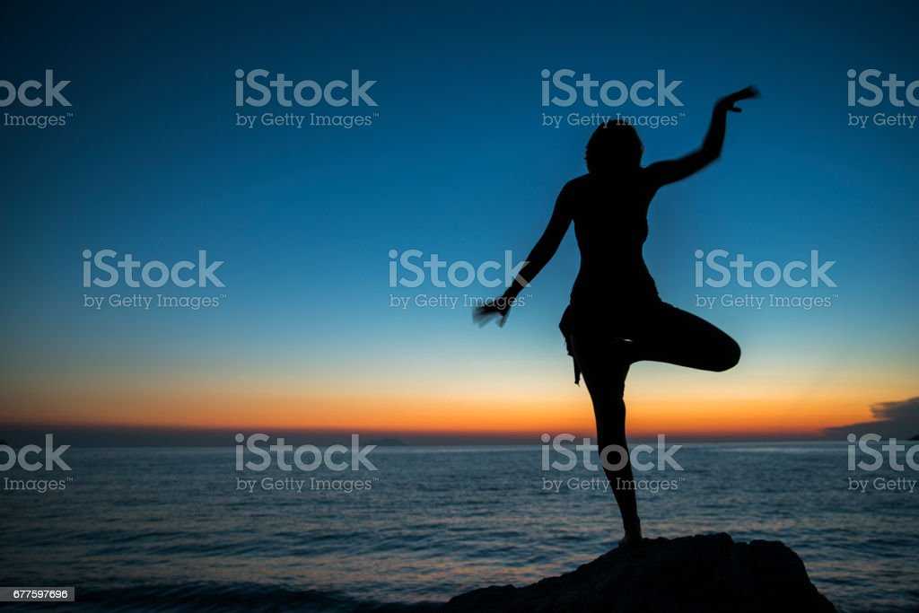 Woman meditating in tree position at beach royalty-free stock photo