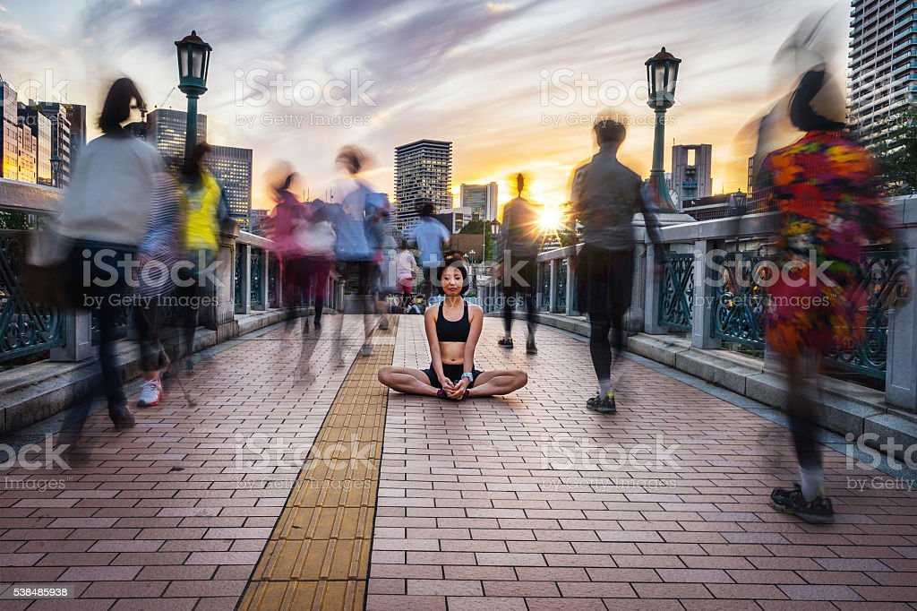 Woman Meditating Into The Crowd At Sunset stock photo
