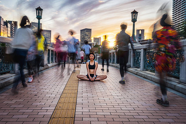 woman meditating into the crowd at sunset - mindfulness stock photos and pictures
