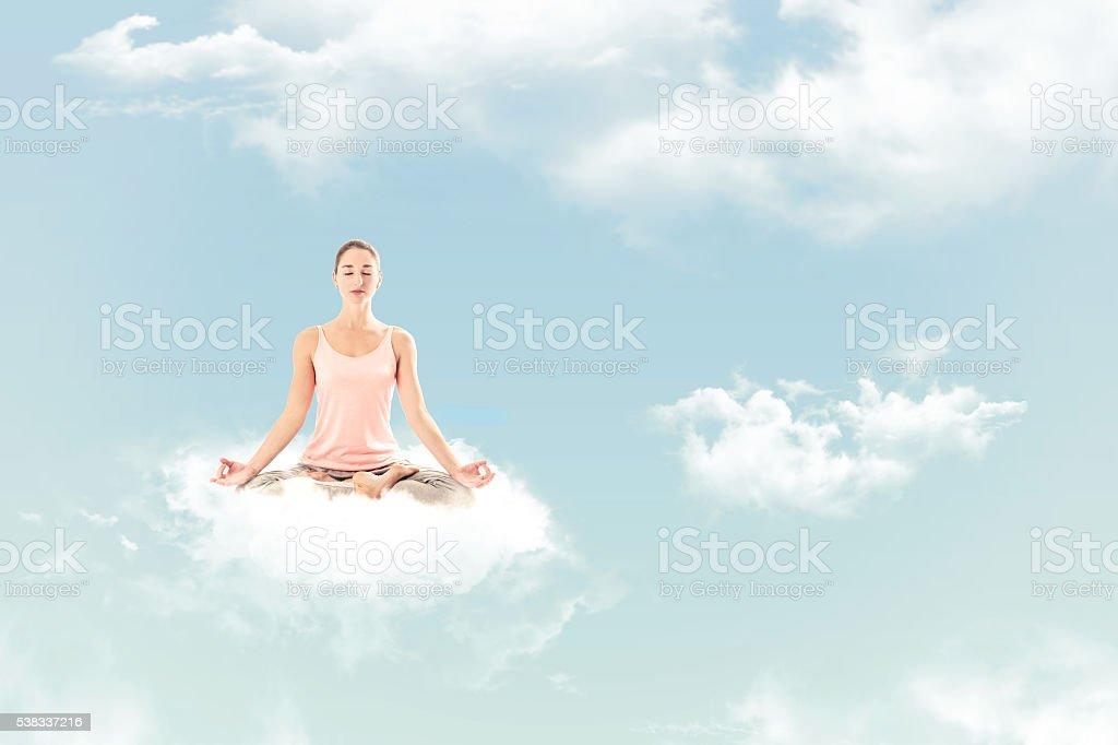 Woman meditating on a cloud. stock photo