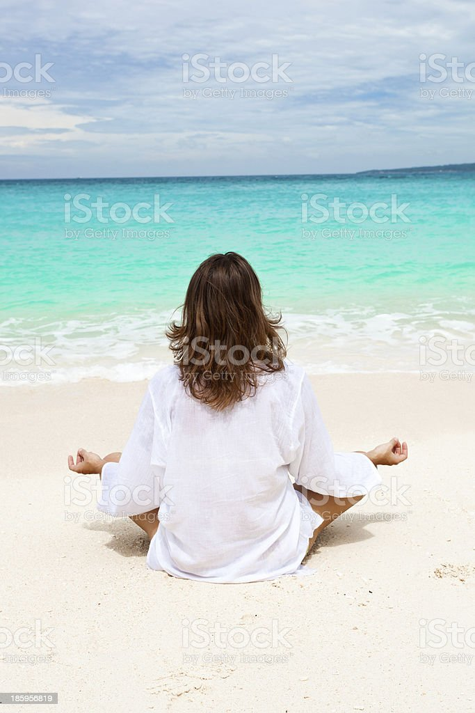 Woman meditating on beach royalty-free stock photo