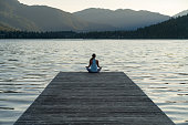 Rear view of female athlete meditating on pier by Lake Alta. Woman in sports clothing exercising during sunrise. She is relaxing in tranquil nature.