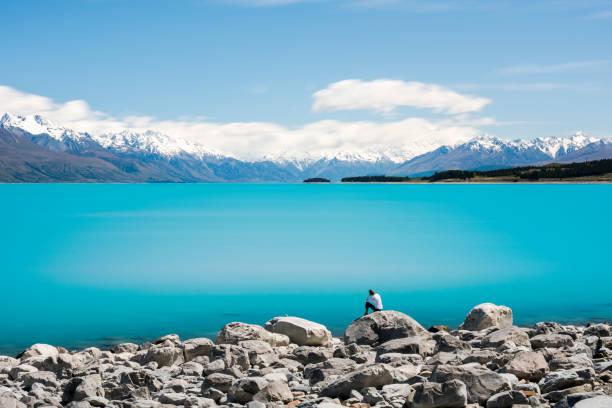 Woman meditating on rock facing Lake Pukaki and Mount Cook stock photo