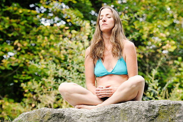 """Woman meditating on rock """"Woman in harmony woth nature, sitting on rocks outdoors and meditating, eyes shutMore like this"""" middle aged women in bikinis stock pictures, royalty-free photos & images"""