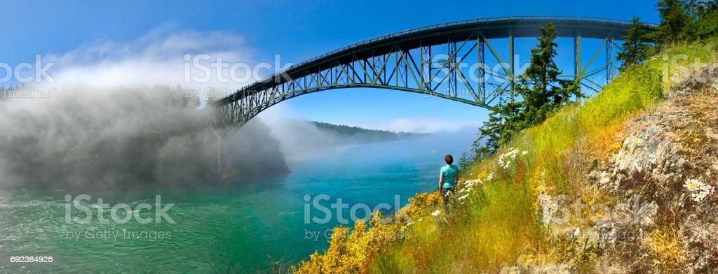 Woman meditating on seashore by the bridge. stock photo