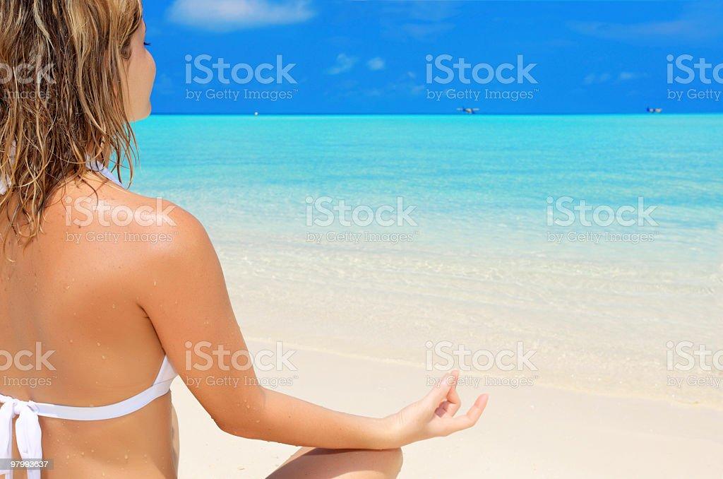 Woman meditating on the beach royalty-free stock photo