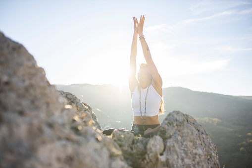 Close up shot of one woman only raising her hands while doing yoga and meditating in nature.