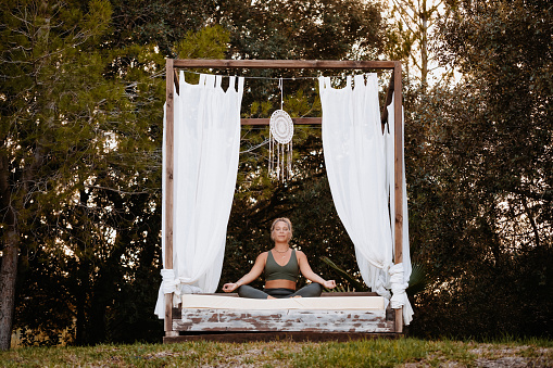 Woman meditating sitting on a balinese outdoor bed, selective focus and  grain added [model with a simple catalogue tattoo]