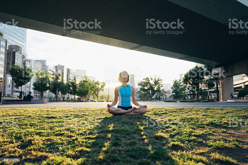 Woman Meditating Under The Bridge At Sunset stock photo