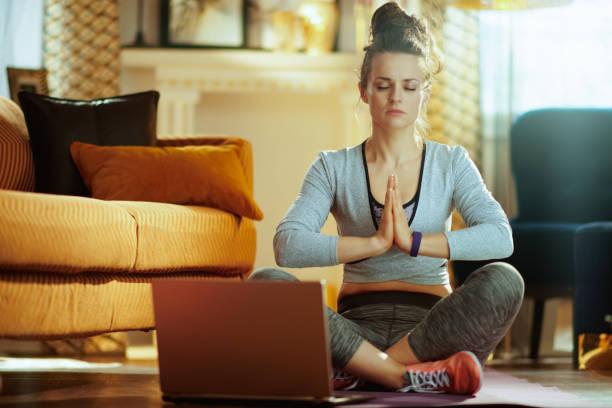 Frau meditiert mit Online-Yoga-Trainingsprogramm in Laptop – Foto