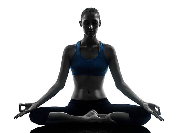Woman meditating while doing yoga one caucasian woman exercising yoga meditating in silhouette studio   on white background lotus position stock pictures, royalty-free photos & images