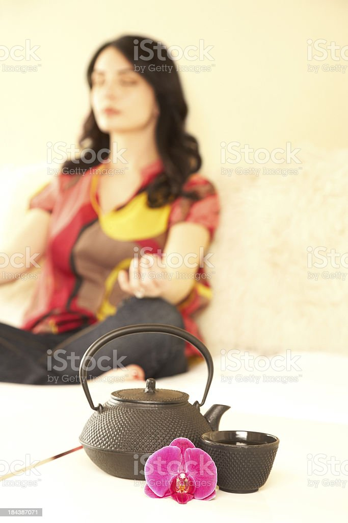Woman meditating with a Japanese tea set and orchid flowers stock photo