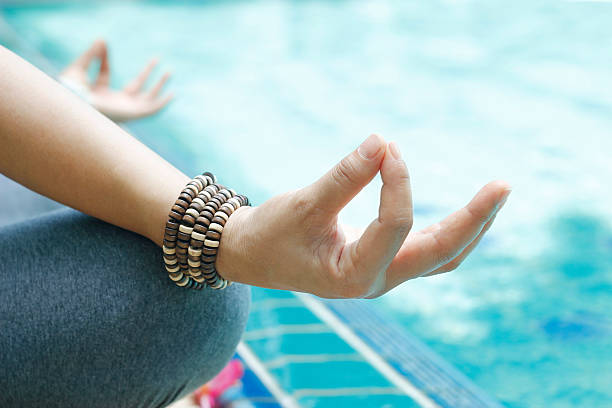 woman meditating with wrist beads in a lotus yoga position - yoga bracelet photos et images de collection