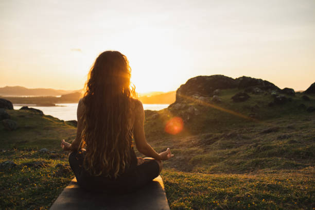 woman meditating yoga alone at sunrise mountains. view from behind. travel lifestyle spiritual relaxation concept. harmony with nature. - mindfulness стоковые фото и изображения