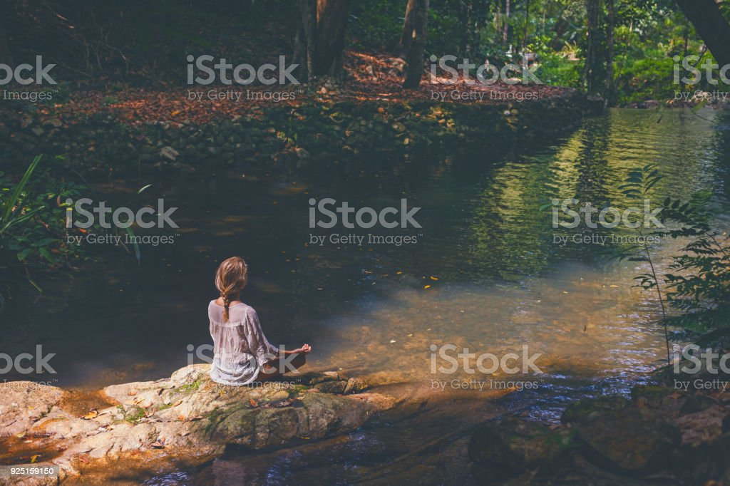 Woman mediting  in tropical forest stock photo