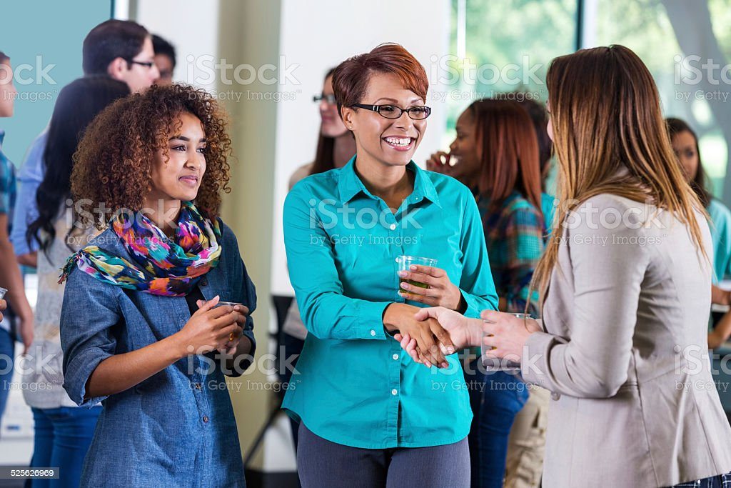 Woman meeting daughter's professor during college orientation mixer stock photo