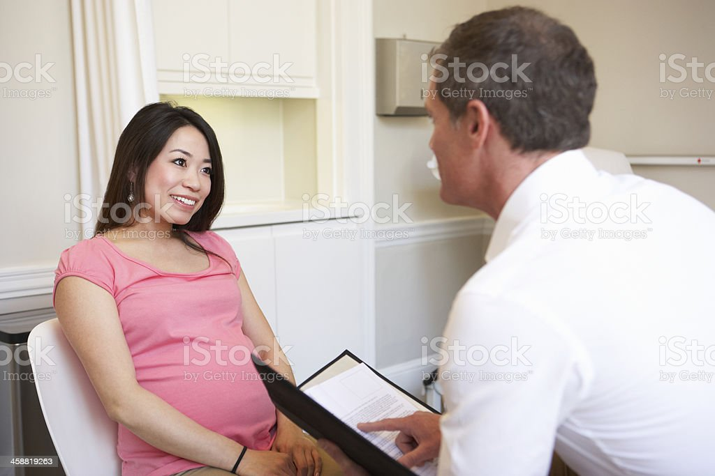 Woman Meeting With Obstetrician In Clinic stock photo