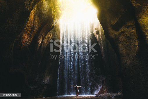 Young woman feeling awe and happiness getting wet staying under the huge waterfall hidden in the cave during bright summer sunny sunset on Bali, Indonesia