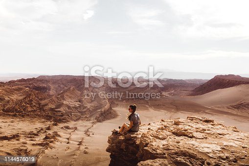 Silhouette of young woman staying at the edge of the cliff and looking at desert landscape during sunset in Atacama region, Chile