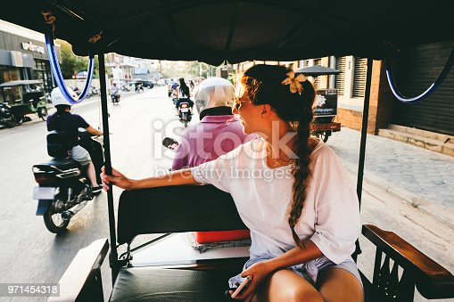 Woman on the road trip by rickshaw meets bright tropical sunset in Siem Reap