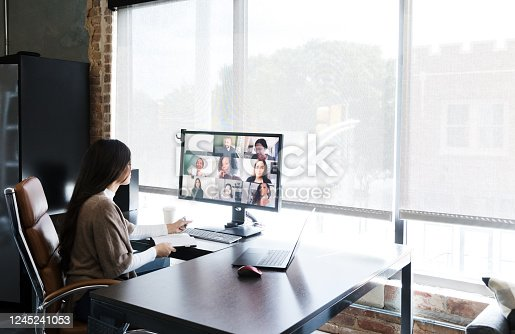 A group of creative professionals meet virtually to discuss and brainstorm ideas. A young female creative professional is working in an office while talking with colleagues who are telecommuting from their homes.