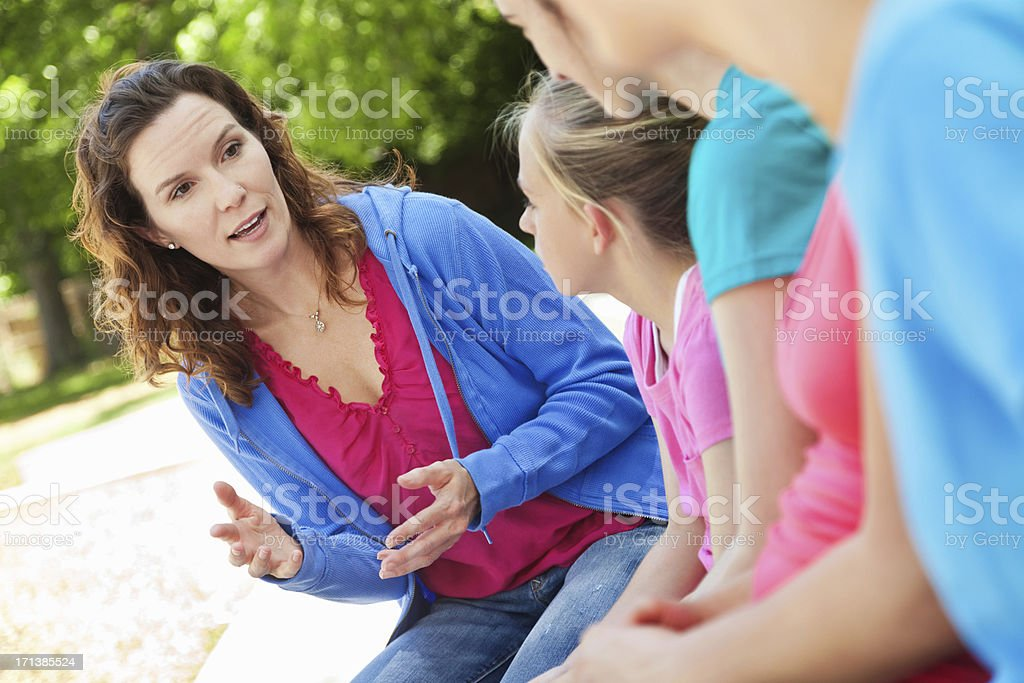 Woman mentoring group of preteen girls at outdoor park royalty-free stock photo