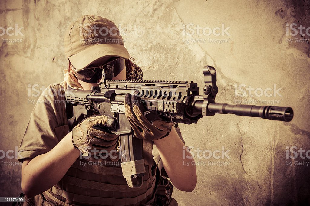 Woman Mercenary Soldier Shooting with Assault Rifle stock photo