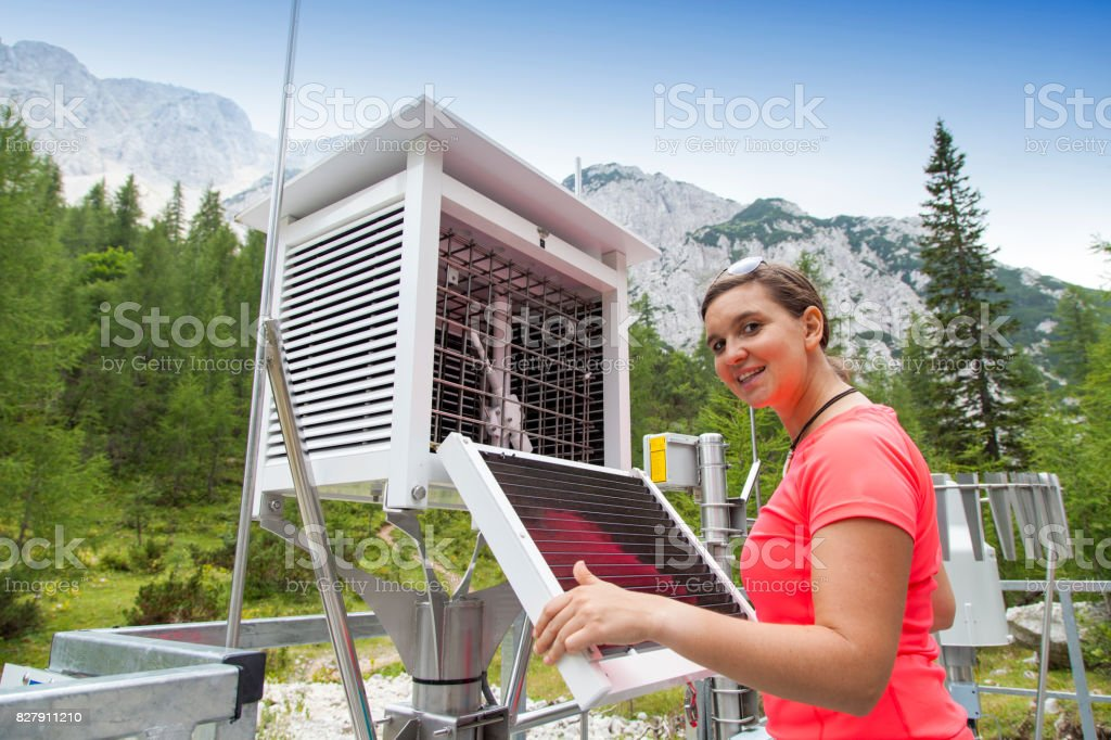 Woman meteorologist reading meteodata in mountain weather station stock photo