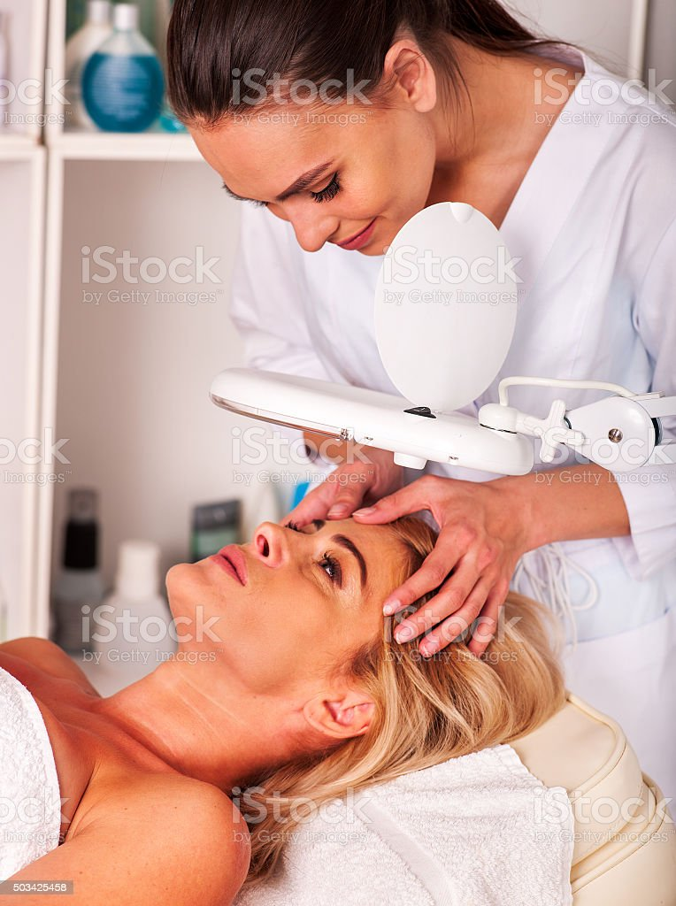 Woman middle-aged in spa salon with cosmetic lamp stock photo