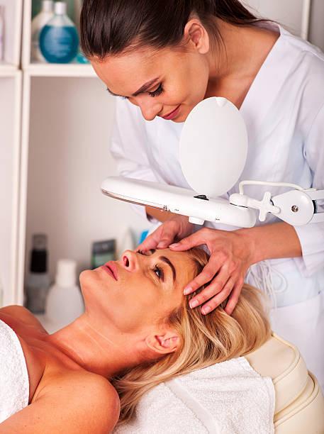 Frau mittleren Alters auf spa-salon mit kosmetischen Lampe – Foto