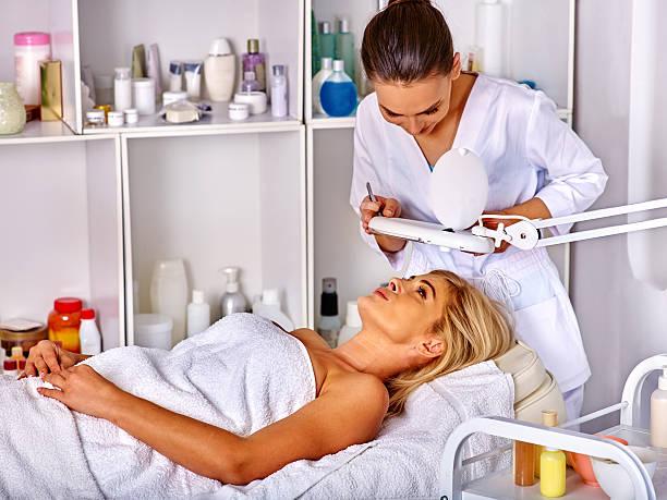 Woman middle-aged lying in spa salon. Tweezing eyebrow beautician. – Foto