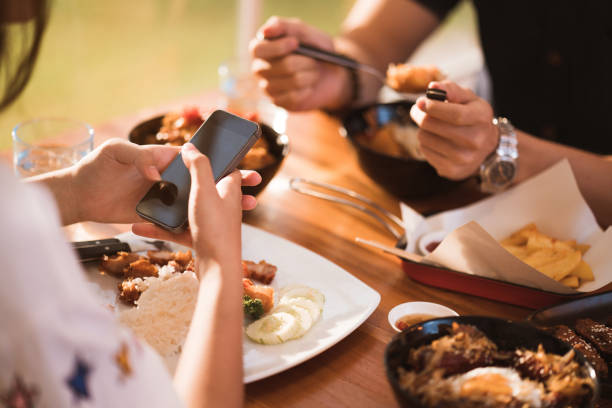 woman mobile while dining with friends in restaurant - eating technology stock pictures, royalty-free photos & images