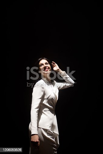 beautiful girl model on stage demonstrates a trouser white suit