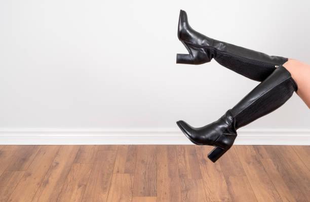 Modelagem joelho preto couro alto botas de mulher - foto de acervo