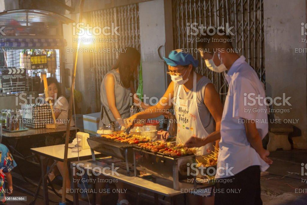 NAKHON PHANOM, Tailandia - 19 de octubre de 2018: monger de mujer venta de barbacoa, Bar-B-Q en Nakhonphanom caminar mercadillo - foto de stock