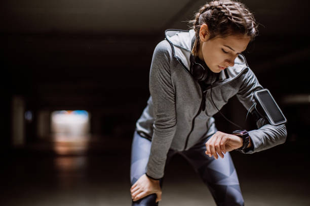 Woman monitoring her progress on smartwatch Young athlete jogging in underground garage woman taking pulse stock pictures, royalty-free photos & images